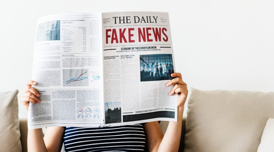 woman holding newspaper in front of face with headline fake news