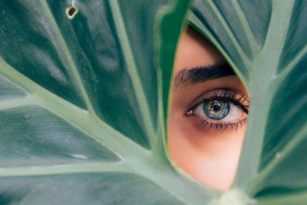 woman's eye peering between leaves