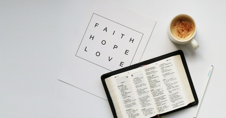 "a bible, cup of coffee and a quote card which reads"" faith, hope, love"""