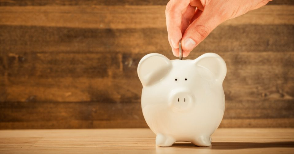a hand putting a coin into a piggy bank
