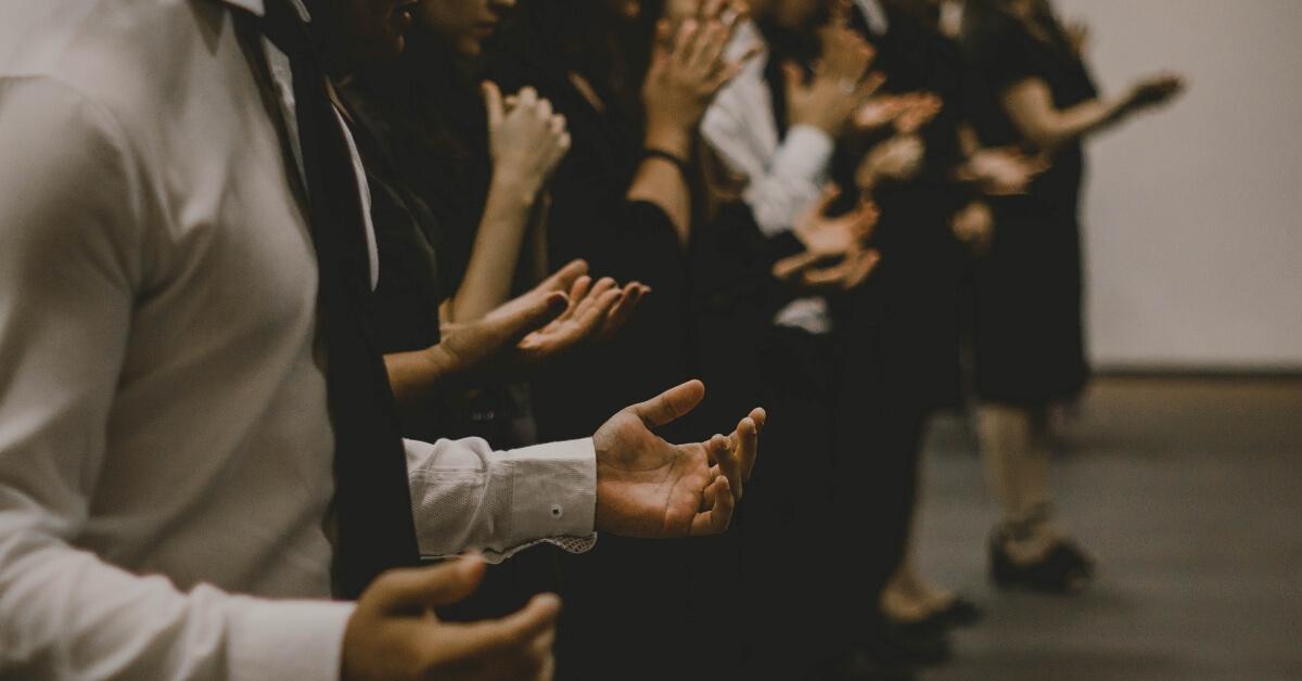 people standing in prayer