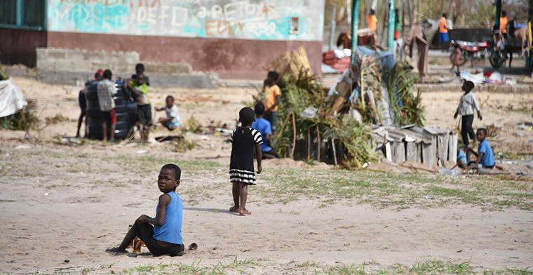 Image of makeshift shelters and children sitting on the ground. Image: World Vision