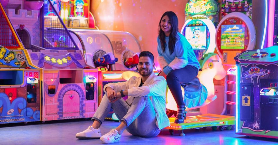man and woman sitting in a colourfully lit arcade