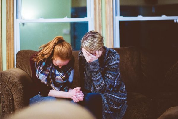 two women sitting on a couch grieving