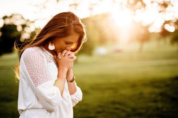 Woman praying in feild