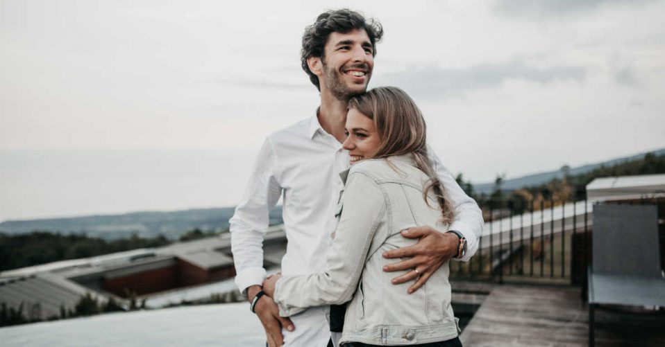 Couple in white hugging on building roof