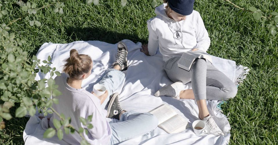 women reading their bibles on white picnic rug in sun