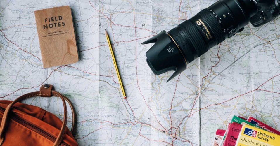 Map, bag, and camera flat lay