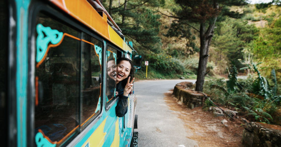 Smiling girl poking her head out of a brightly painted bus