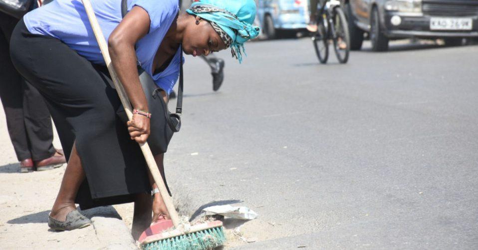 Woman sweeping gutter