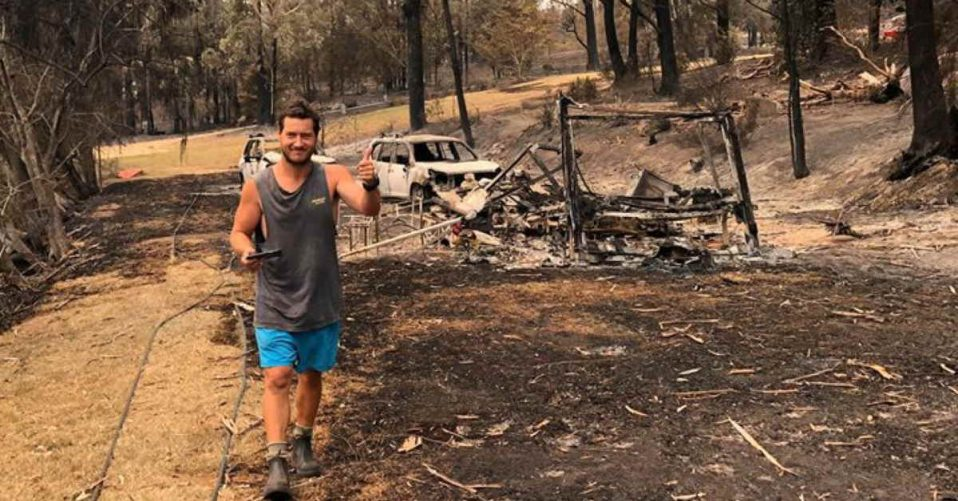 Andrew Flaxman walking in burned bushland with his burnt out car and caravan behind him