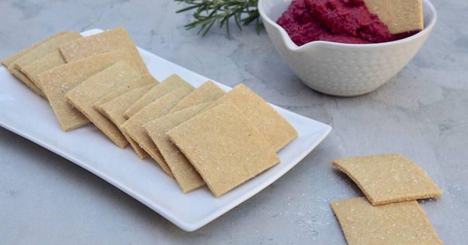 crackers on a plate with a bowl of beetrot dip in the background