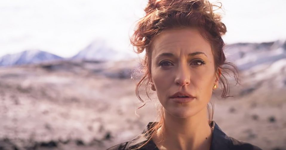 Lauren Daigle with desert background looking directly at camera
