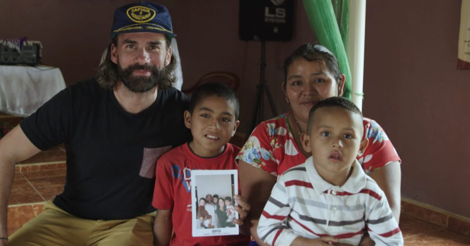 Rend Collective Band Member Gareth sitting with sponsor child and his family