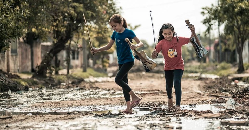 girls with violins playing in the mud
