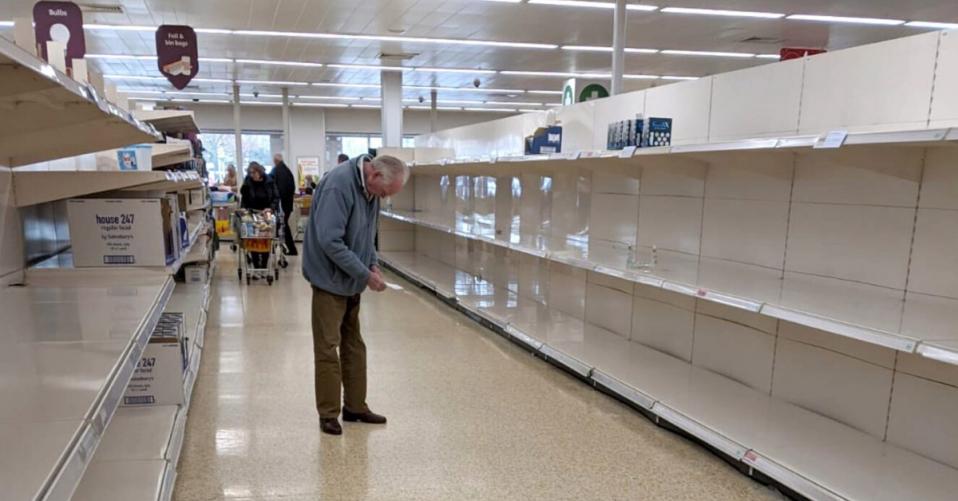 elderly man in empty shopping aisle