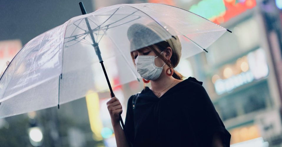 Women wearing mask holding an umbrella