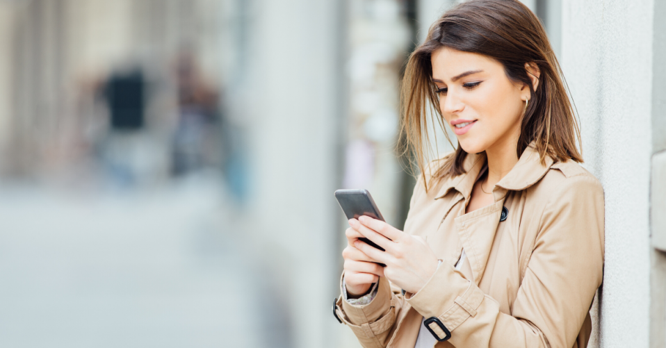 woman leaning against wall smiling looking down at mobile phone
