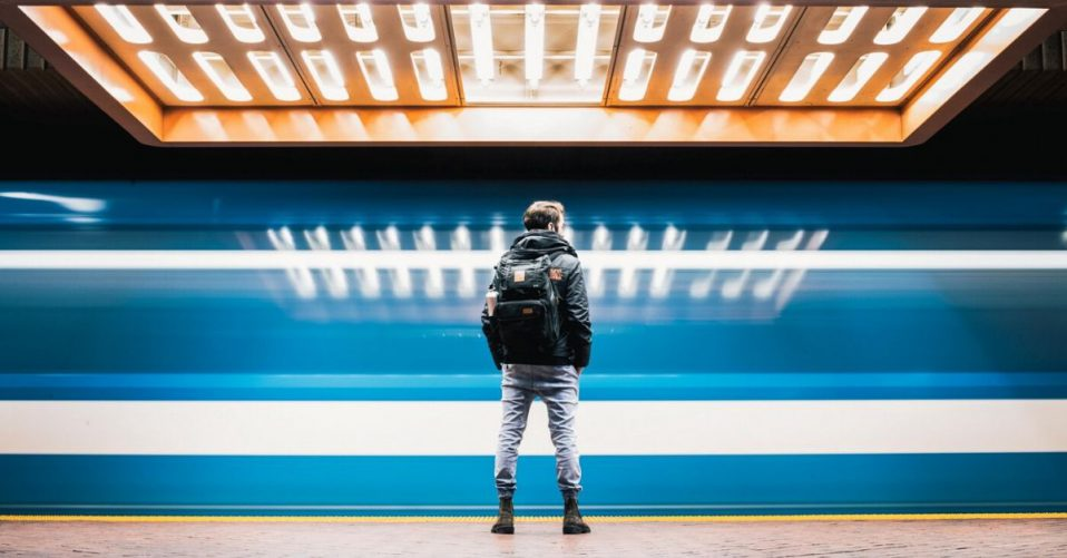 photo of a man standing in a brightly lit subway tunnel