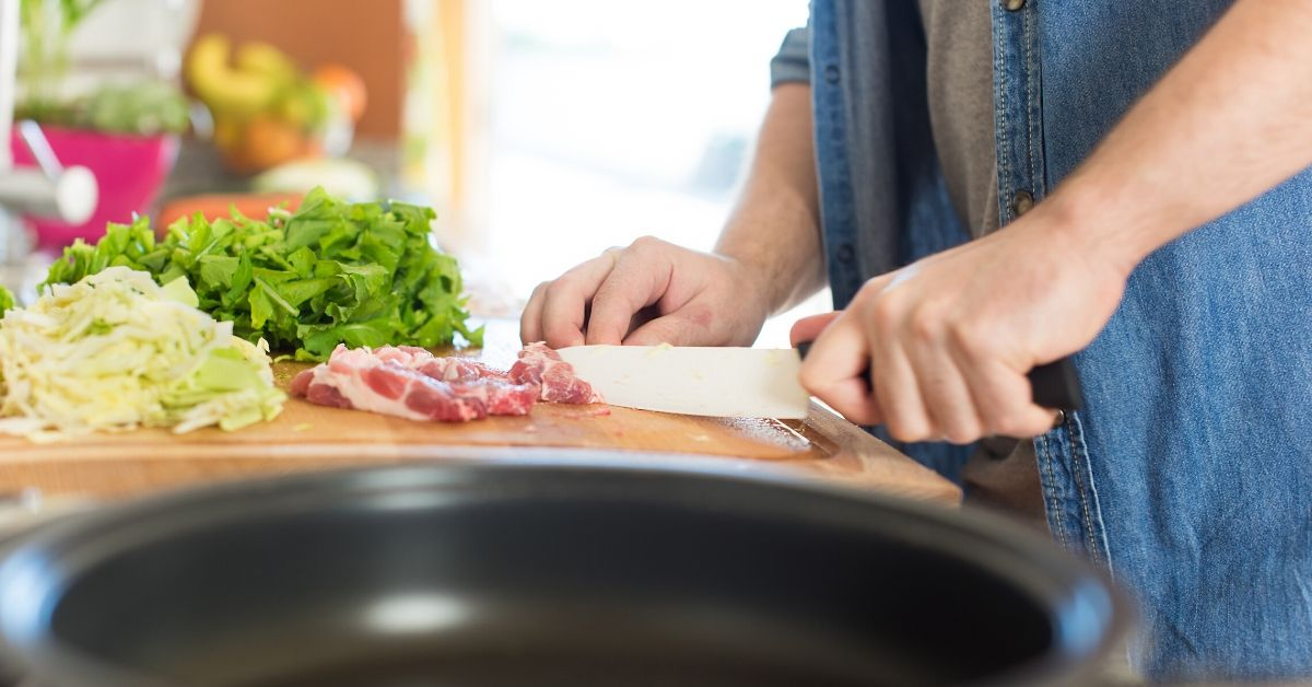 person chopping veges and meat in a kitchen
