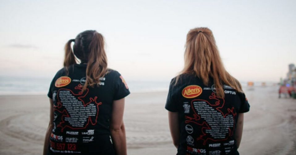 photo of the backs of two girls wearing red frogs shirts on the beach