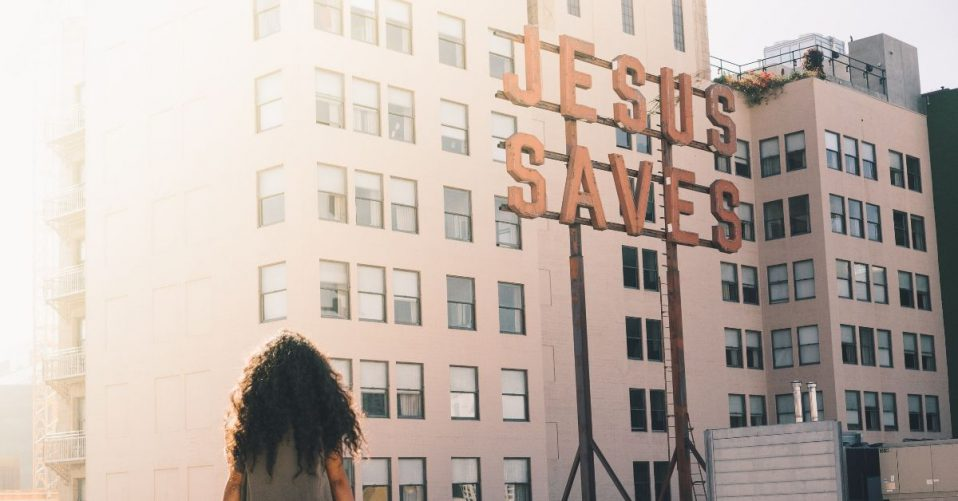 """photo of a woman sitting on a wall overlooking skyrises beside a sign which says """"jesus saves"""""""