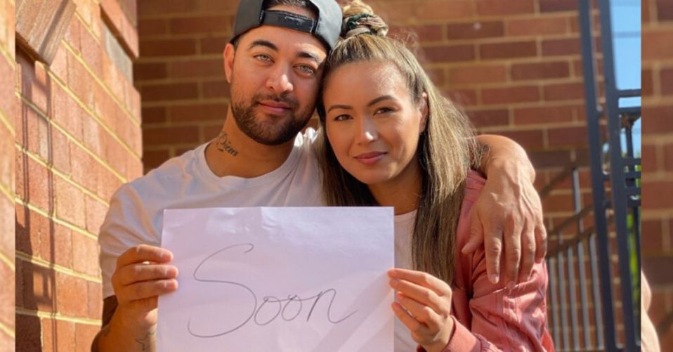 A photo of singer chris sebastian and his wife tash sittg on stairs holding a paper with soon written on it