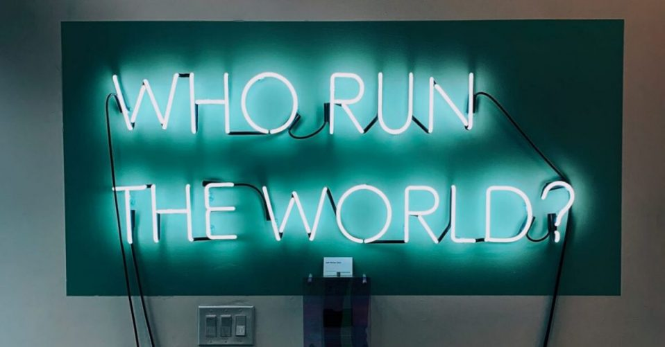 teal neon lights on a tv screen which says who run the world