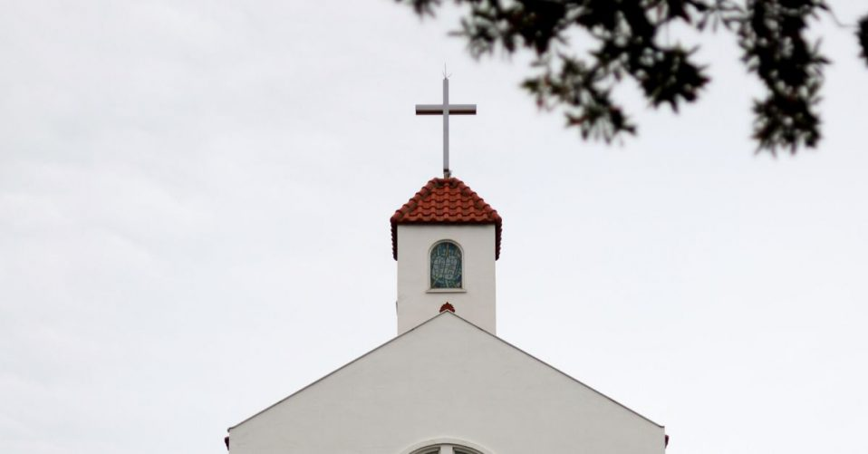photo of church's roof which has a cross on top