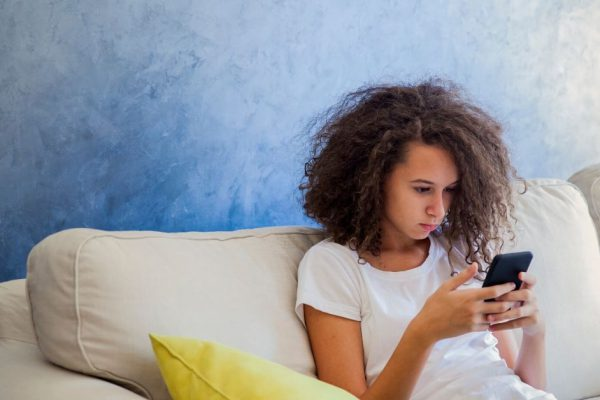 photo of a young girl sitting on a couch looking at her phone