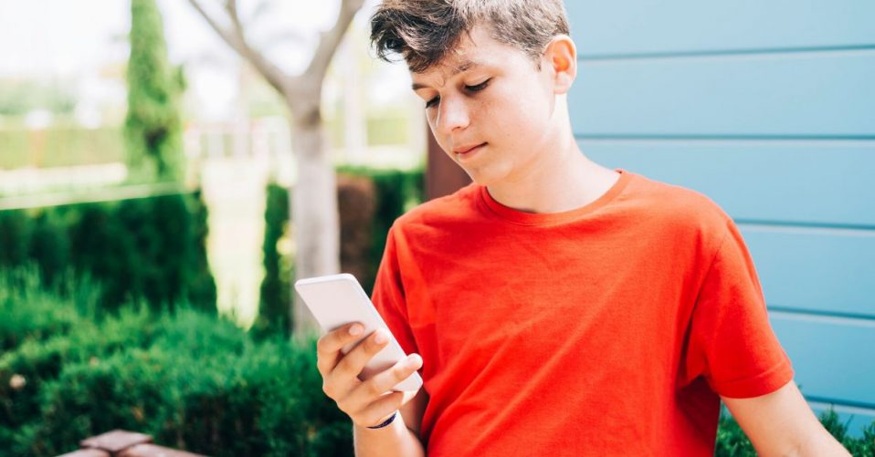 photo of a boy wearing a red shirt on his phone outside in the yard