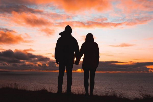 photo of a silhouette of a couple holding hands at dusk looking over the ocean