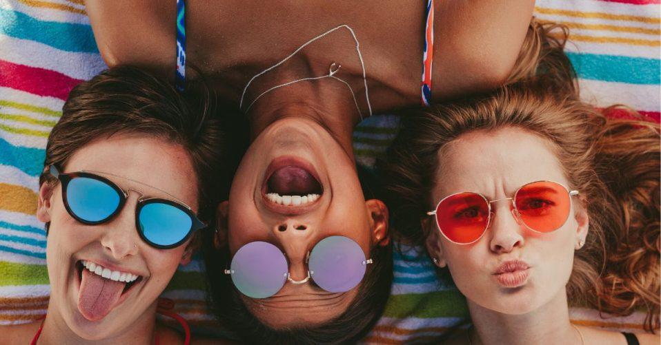 photo of 3 girls wearing colourful sunglasses