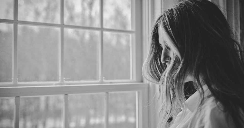 black and white photo shows a woman standing at a window with hair covering her face