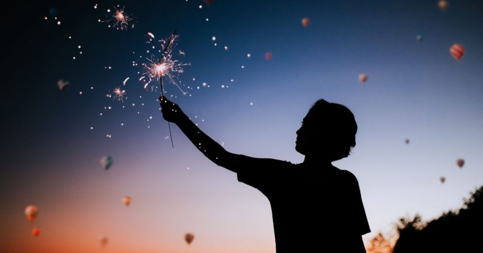 photo depicts a silhouette of a boy at sunset holding a sparkler to the sky
