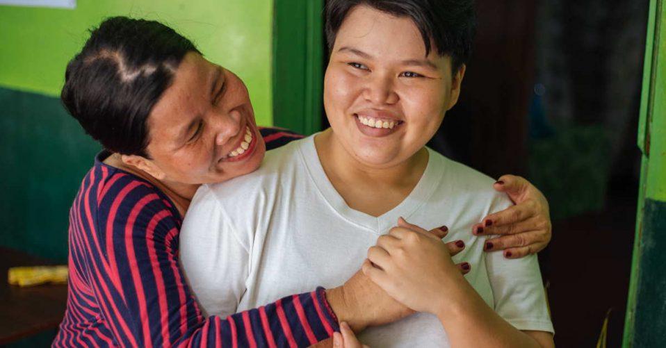 Mum giving daughter hug both have big smiles