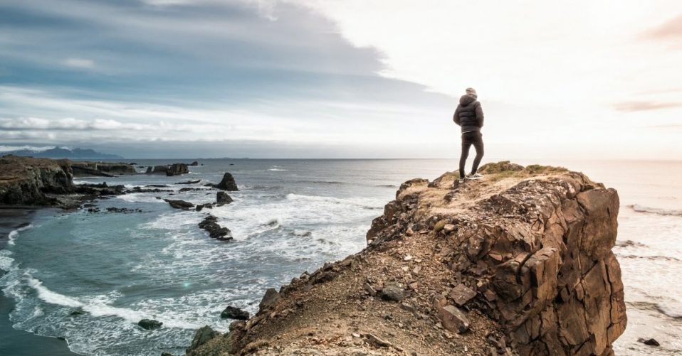 man standing on a hill overlooking the ocean