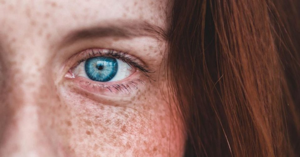 a freckled face and close up of piercing blue eyes
