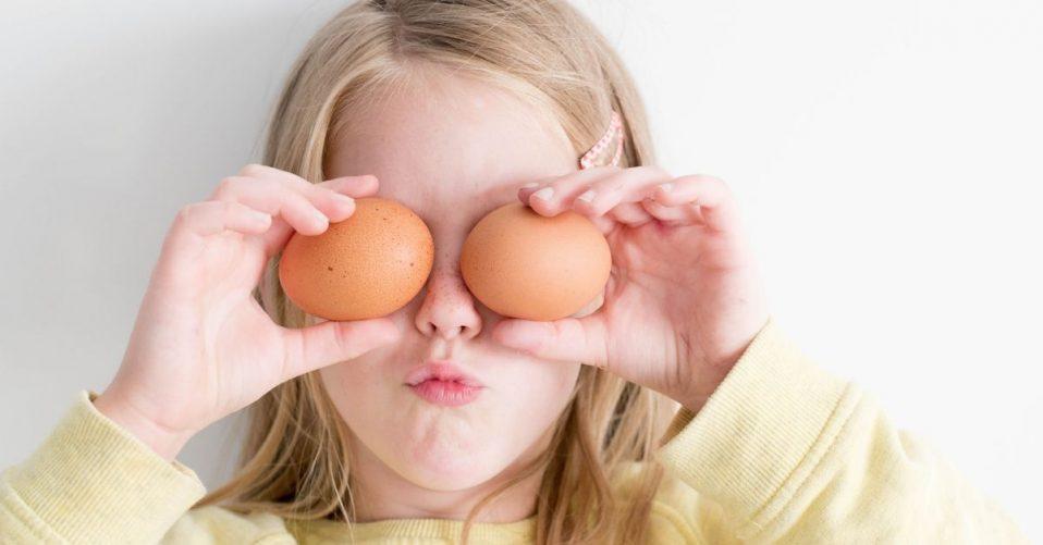girl holding eggs over her eyes